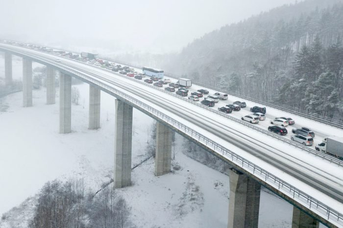 Aerial view over a highway bridge during a heavy snowfall in winter