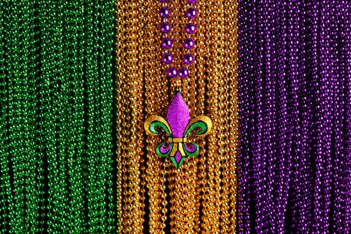 Green, gold, and purple Mardi Gras beads with Fleur de lis background