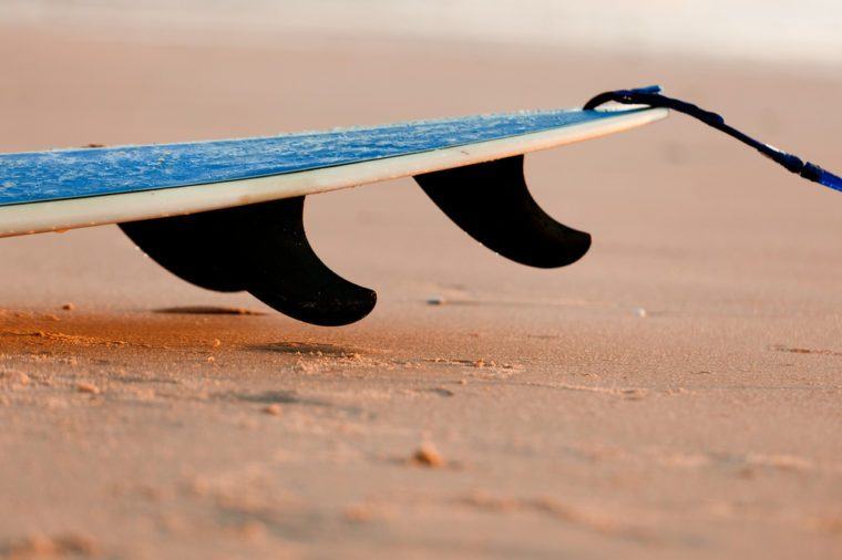 Tail of a surfboard on the sand with three fins