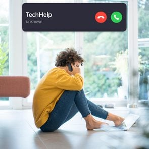 woman using a computer while on the phone with incoming call interface overlay