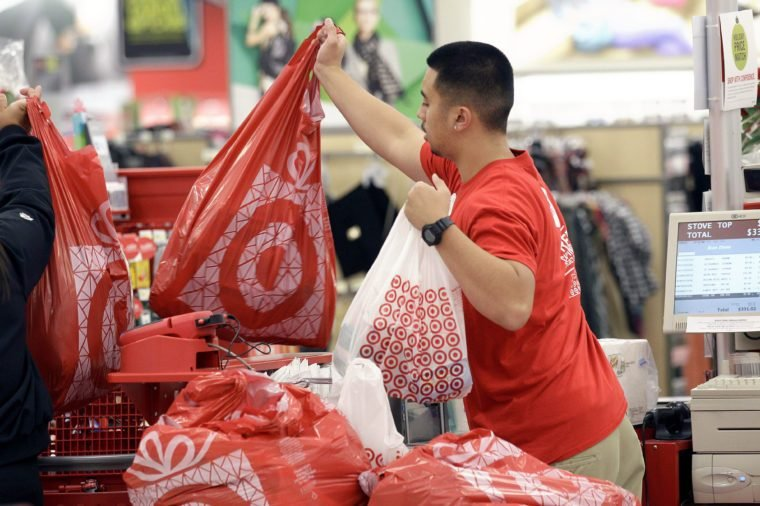 A Target employee hands bags to a customer at the register.