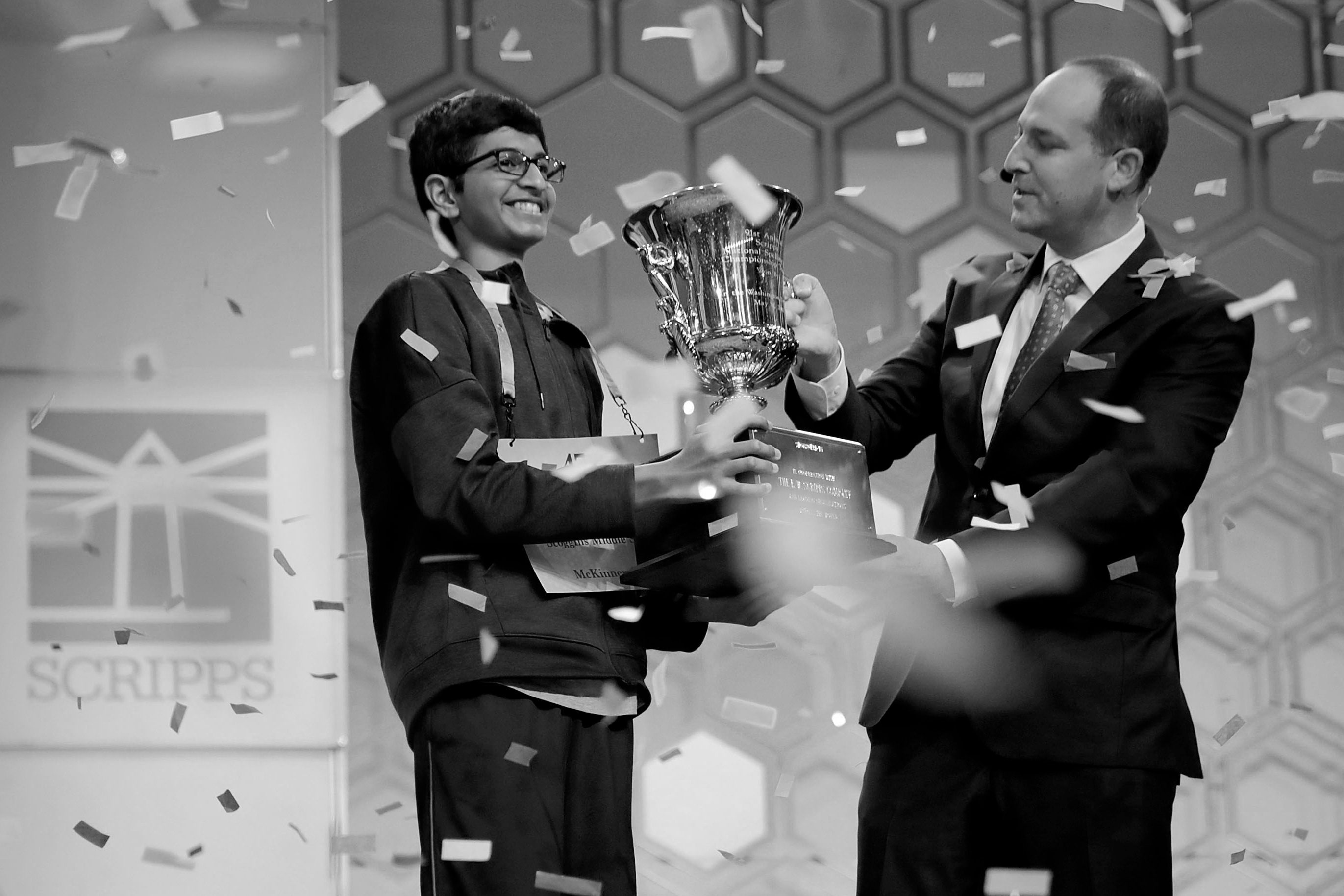 Karthik Nemmani (L) poses with the championship trophy and E.W. Scripps Company CEO Adam Symson after Nemmani correctly spelled the word 'koinonia' to win the 91st Scripps National Spelling Bee at the Gaylord National Resort and Convention Center May 31, 2018 in National Harbor, Maryland.