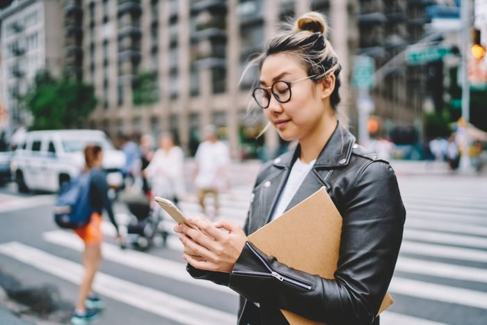 Young attractive female blogger in glasses for eye protection sharing news with followers via smartphone application.Gorgeous hipster girl strolling at urban setting with gadget during leisure time