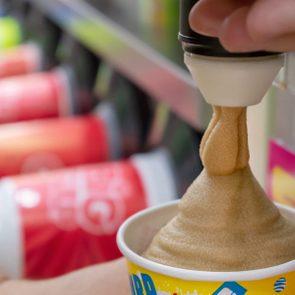 BANGKOK, THAILAND - DECEMBER 18: Slurpee machine fills up a paper cup with Coca-Cola flavored Slurpee in 7-Eleven on Petchkasem 69 in Bangkok on December 18, 2018.