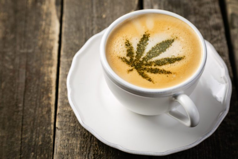 Cannabis coffee - marijuana leaf on coffee foam, rustic wood background