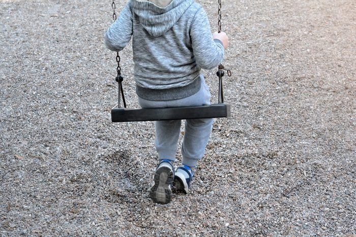 Boy Sitting On A Swing - Lonely Child Concept