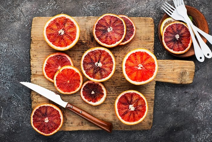 Fresh red oranges with slices on a vintage old cutting wooden board on a gray background. Top View