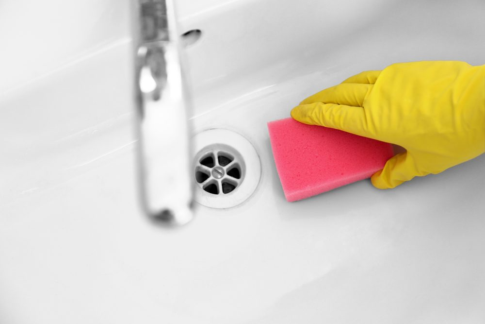 Female hand with sponge cleaning a sink in the bathroom