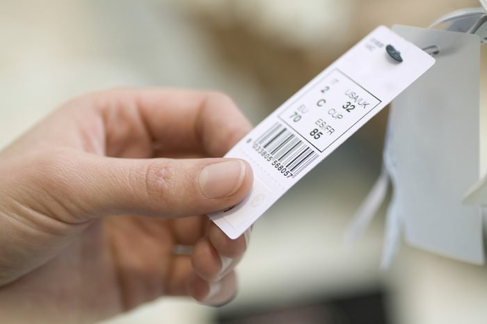 Closeup of woman's hands holding clothes tag in store