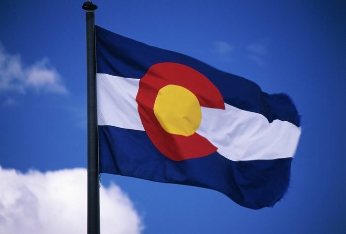 This is the Colorado State Flag, waving in the wind situated on a flag pole. It is set against a blue sky. At the center of the flag is a large capital C.