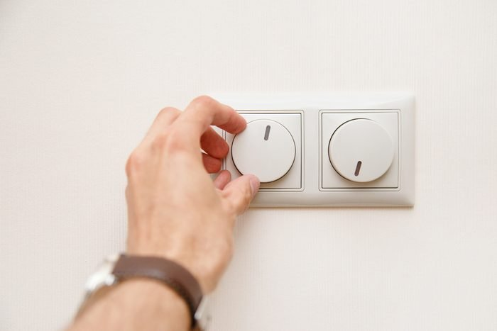 Saving energy concept: Human hand turning down electrical light dimmer switch.
