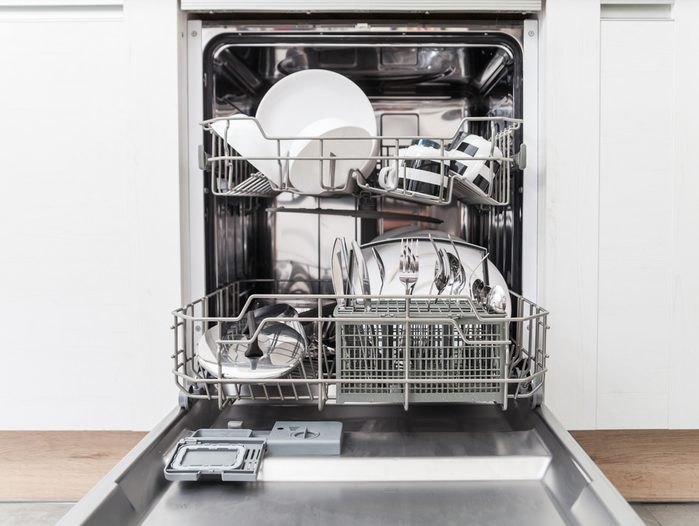 Open dishwasher with clean dishes in white kitchen, front view