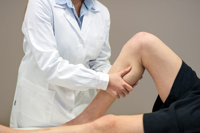 Female doctor physiotherapist practicing massage to her leg male patient in medical center.