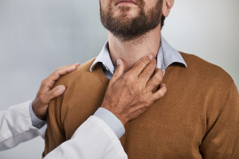 Close up of doctor hand checking thyroid gland of patient for further action and recommendations