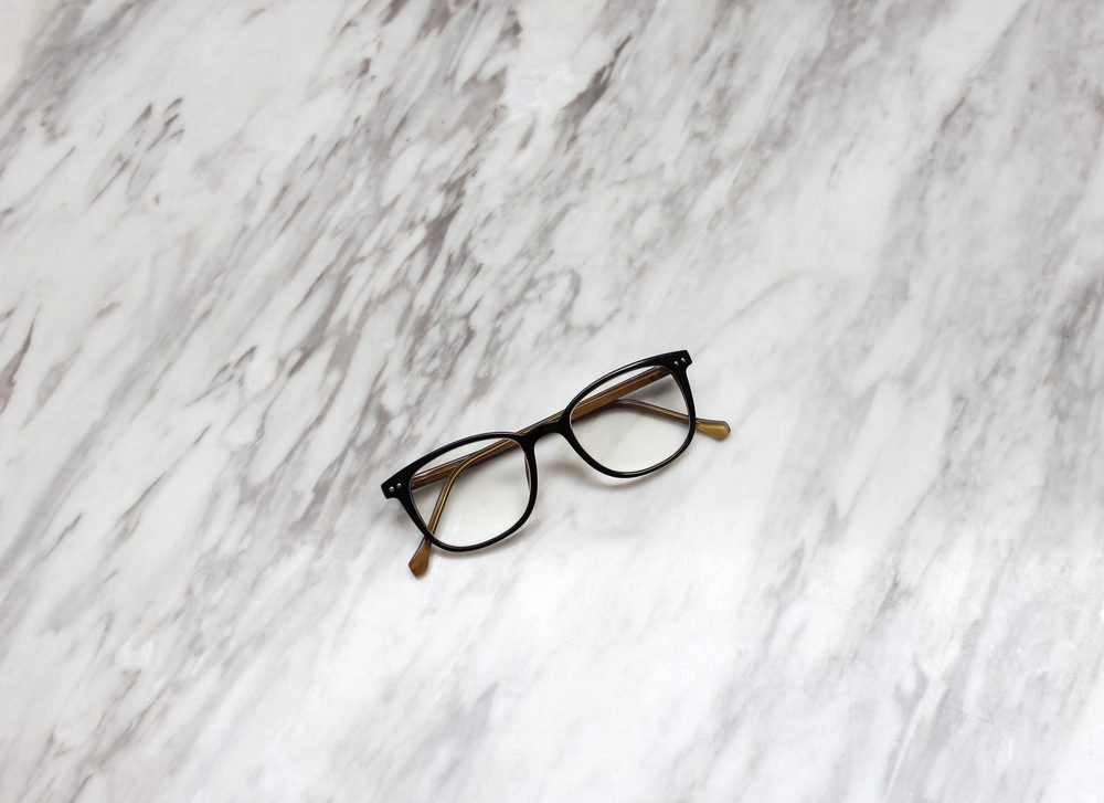 Eyeglasses on black and white marble table texture