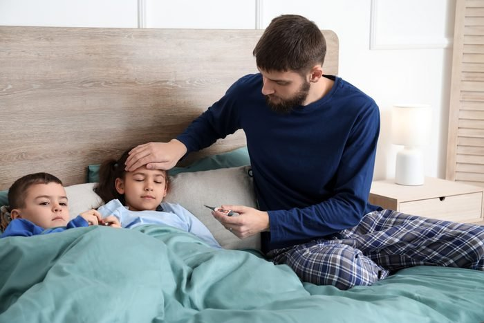 Young father taking care of sick children at home