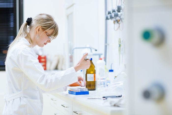 female researcher carrying out research experiments in a chemistry lab (color toned image)