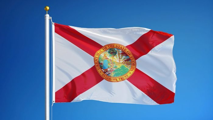 Florida (U.S. state) flag waving against clear blue sky, close up, isolated with clipping path mask alpha channel transparency, perfect for film, news, composition