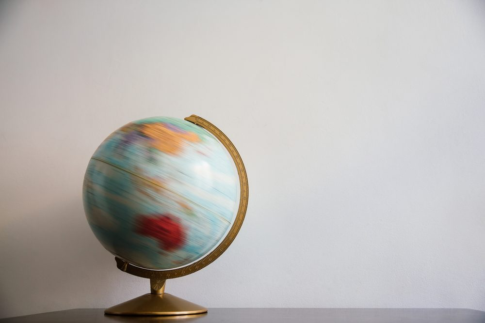 Globe model spinning on dark wooden desk. White wall empty space background.