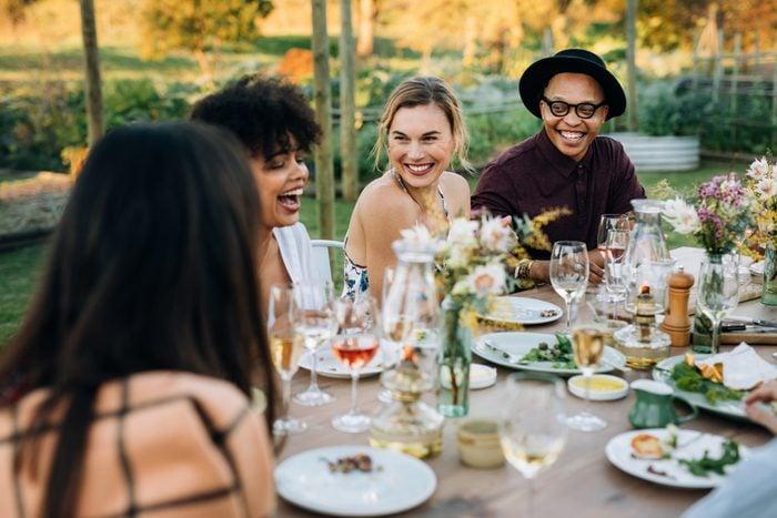Group of friends enjoying outdoor party in home garden. Millennials  enjoying summer meal at restaurant.