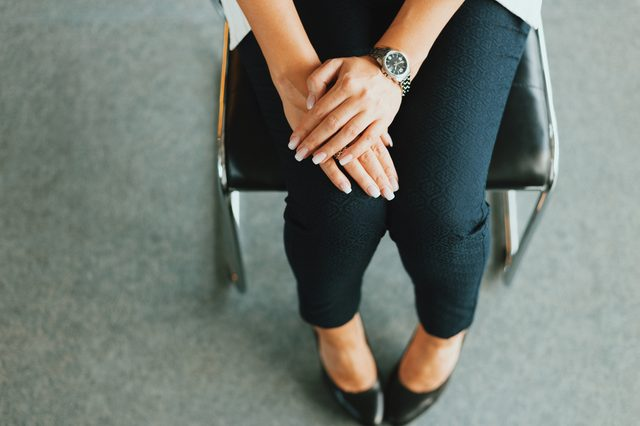 Woman in pants is sitting on the chair. Her arms on the legs. Waiting