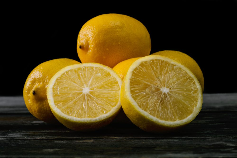 Fresh lemons on an old wooden table. Selective focus and small depth of field.