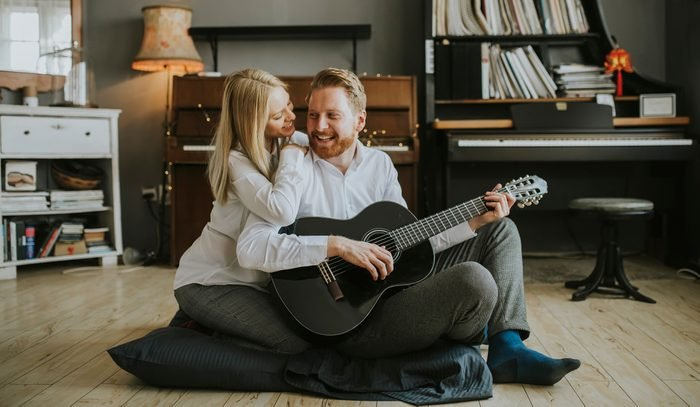 Lovely young couple playing guitar in the room