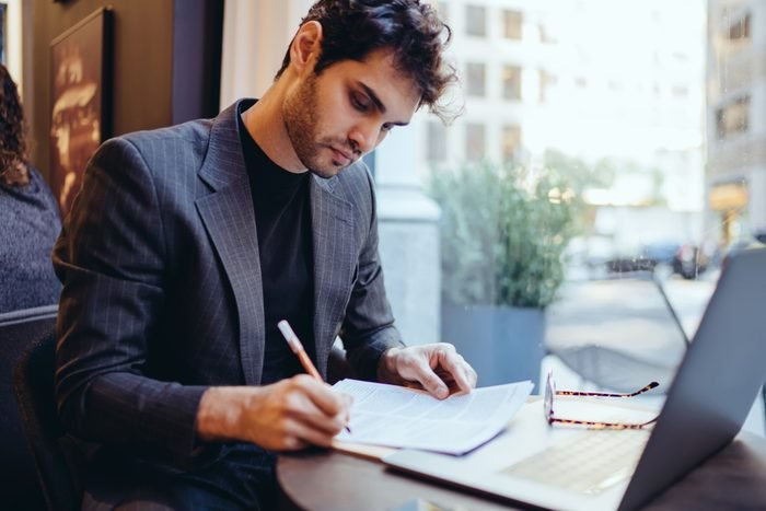 Young handsome caucasian businessman  in trendy suit writing information on financial papers for banking on laptop computer, serious confident male doing paperwork remotely indoors in coffee shop