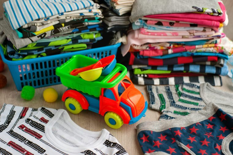 Many children's clothes. Clothes for children are stacked in the laundry basket and in a pile. Children's clothing made of soft fabric. Toy dump truck and clothes for the boy. T-shirts and panties.