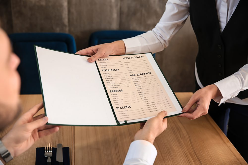 Young waitress showing man a menu in restaurant