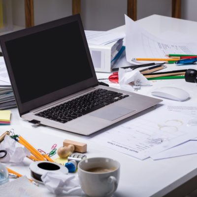 An Open Laptop On The Messy Desk With Coffee Cup And Documents At Workplace