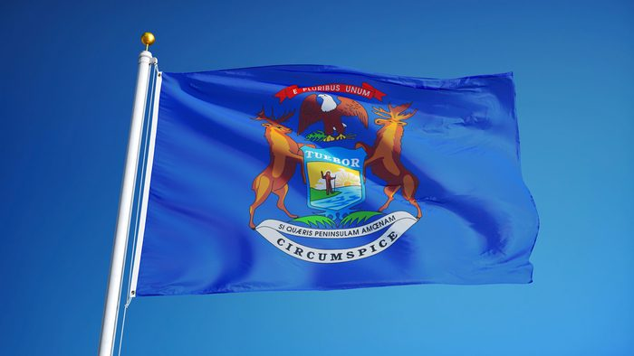 Michigan (U.S. state) flag waving against clear blue sky, close up, isolated with clipping path mask alpha channel transparency, perfect for film, news, composition