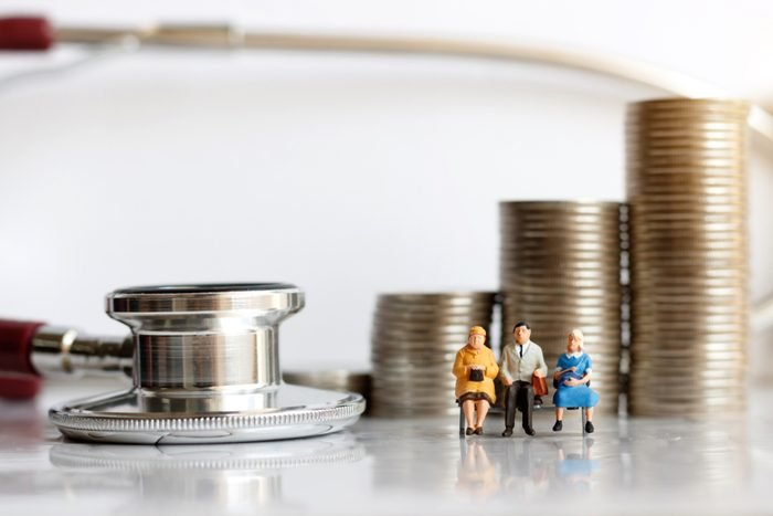 Miniature people sitting on syringe wit stethoscoper and stack of coins, business and health care concept.