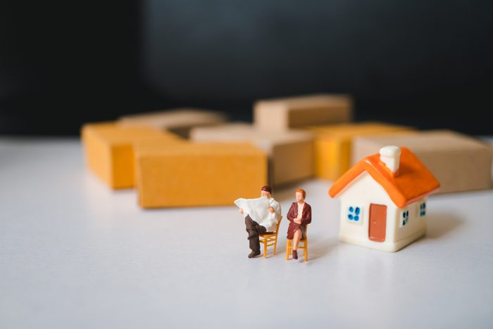 Miniature people, husband and wife relaxing on mini house and stack cardboard boxes background using as logistics and home business concept