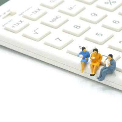 Miniature 3 people sitting on white calculator using as background business concept with copy space.