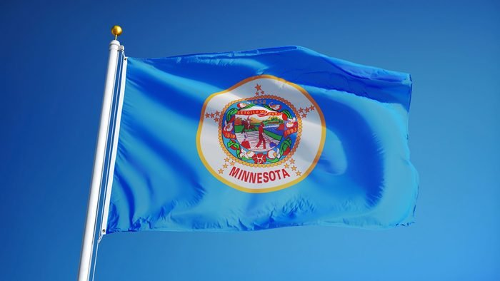 Minnesota (U.S. state) flag waving against clear blue sky, close up, isolated with clipping path mask alpha channel transparency, perfect for film, news, composition