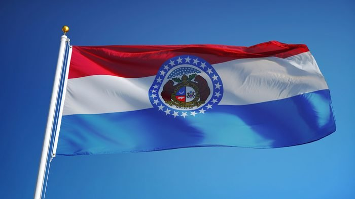 Missouri (U.S. state) flag waving against clear blue sky, close up, isolated with clipping path mask alpha channel transparency, perfect for film, news, composition