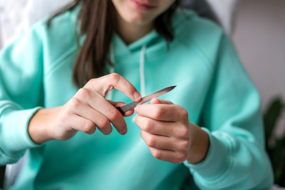 young girl handles nails with nail file close up