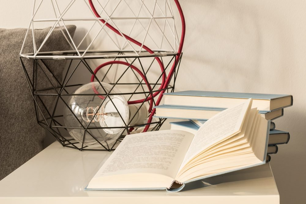 White nightstand with wire lampshade and large incandescent bulb standing next to a pile of books in blue cover, one of which is lying open