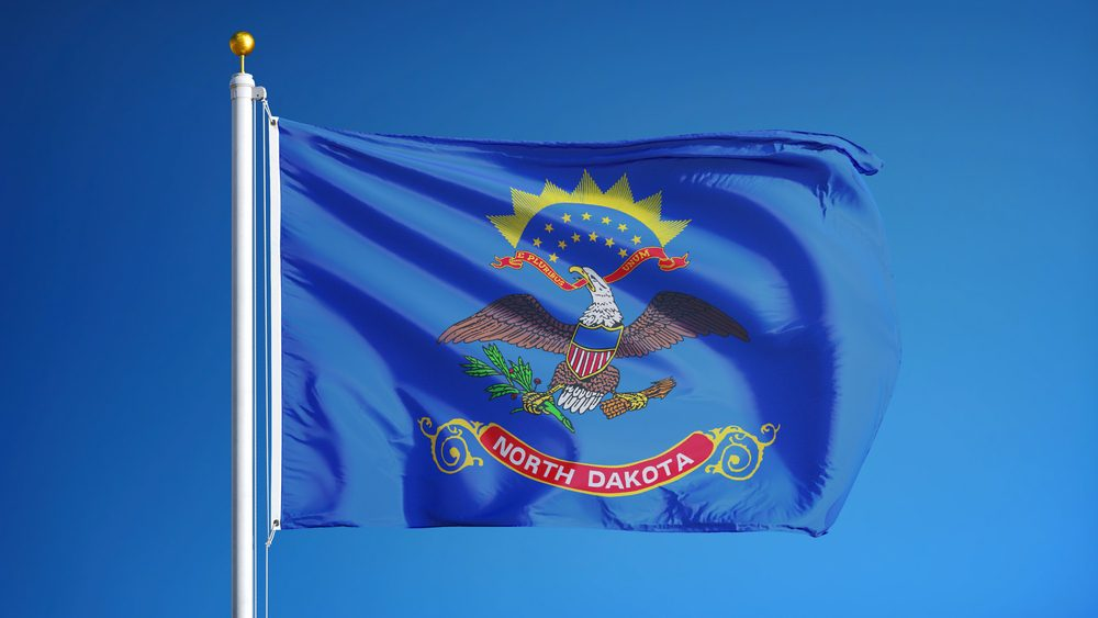 North Dakota (U.S. state) flag waving against clear blue sky, close up, isolated with clipping path mask alpha channel transparency, perfect for film, news, composition