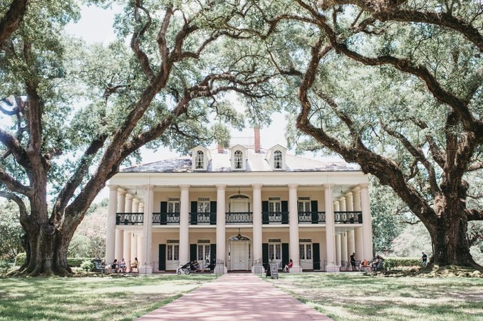 Oak Alley Plantation, Vacherie, St. James Parish, Louisiana / United States - June 28-2018: oak alley big house photo with canopy of oak trees leading to the house and tourist.