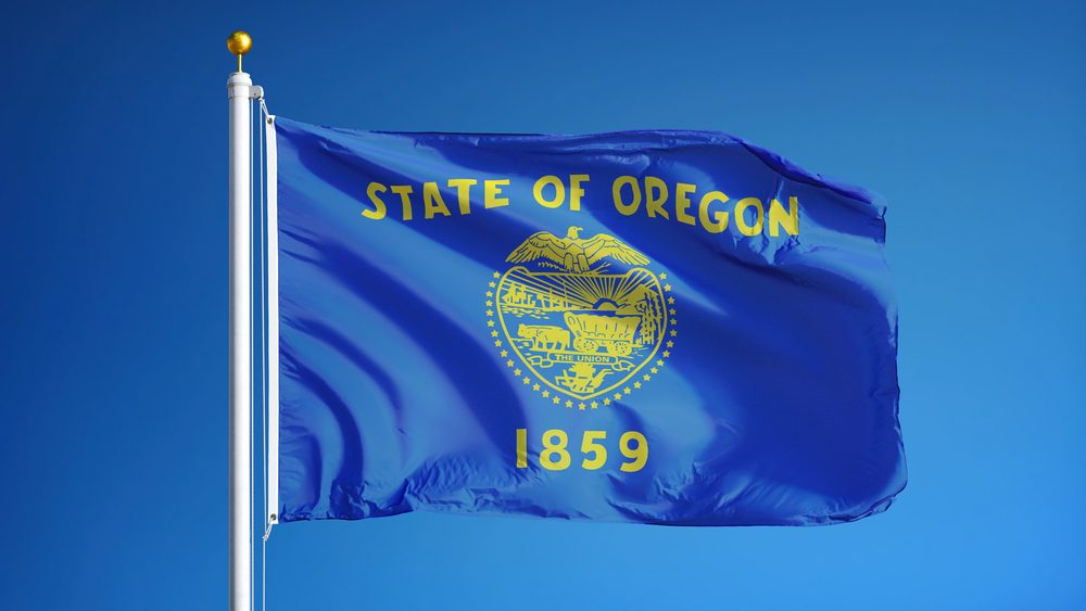 Oregon (U.S. state) flag waving against clear blue sky, close up, isolated with clipping path mask alpha channel transparency, perfect for film, news, composition