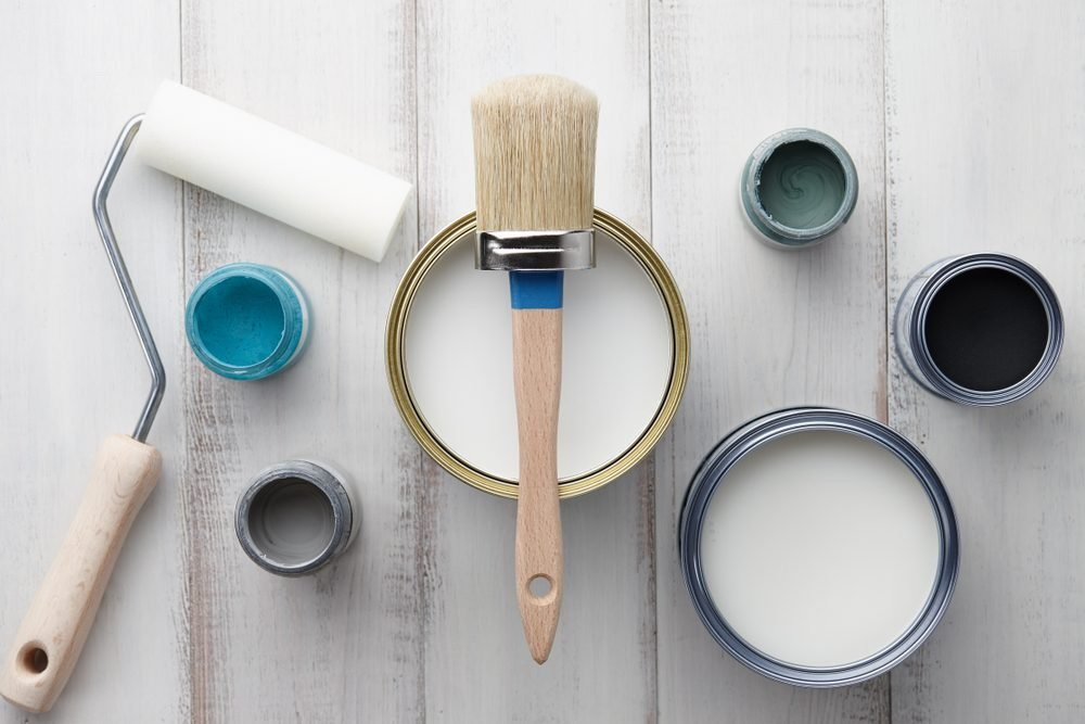 Paint brush, sponge roller, paints, waxes and other painting or decorating supplies on white wooden planks, top view