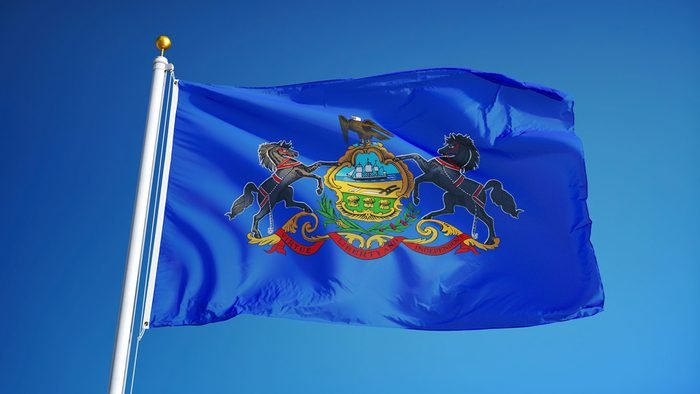 Pennsylvania (U.S. state) flag waving against clear blue sky, close up, isolated with clipping path mask alpha channel transparency, perfect for film, news, composition