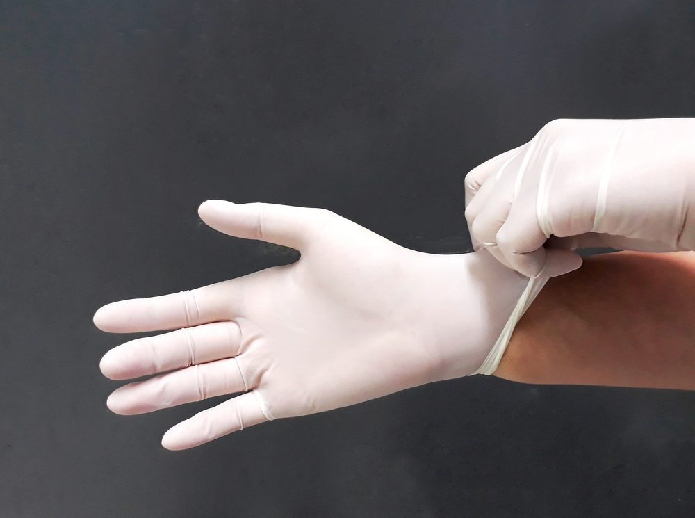 Female hands with disposable latex gloves wearing gesture, selective focus.