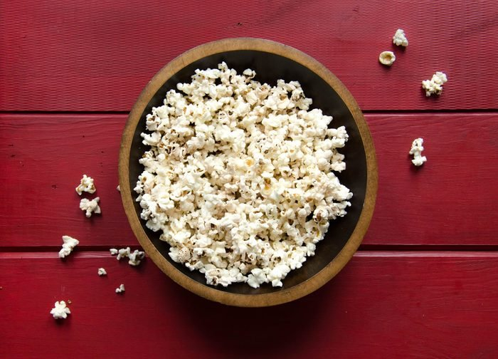 Bowl of popcorn in wooden bowl on red wood background