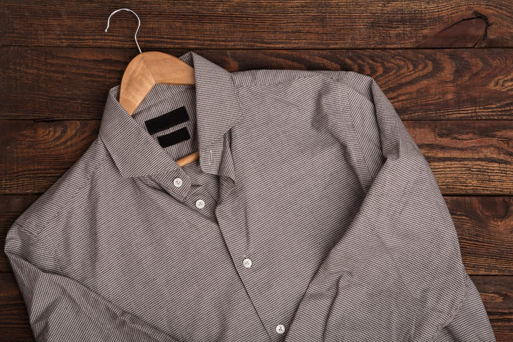 Business classic men's shirt with houndstooth pattern print. Casual outfit on brown wooden grunge background