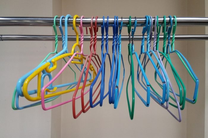 Colorful plastic clothes hangers hang on cloth line.