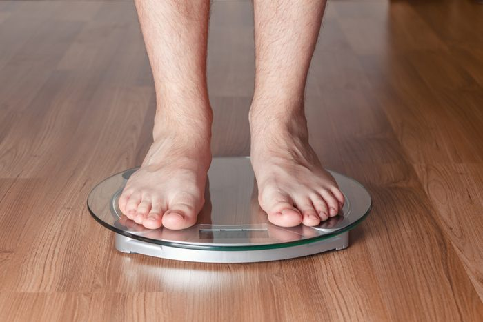 Men's feet on the scales