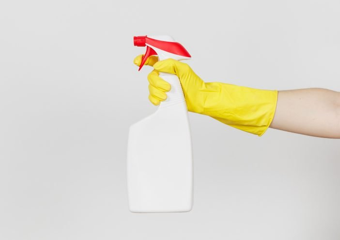Close up of female hand in yellow gloves click on white spray bottle with cleaner liquid with place for text isolated on white background. Cleaning supplies concept. Copy space for advertisement.